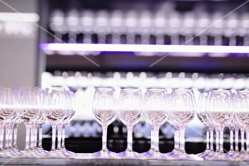 A row of empty wine glasses on a restaurant counter