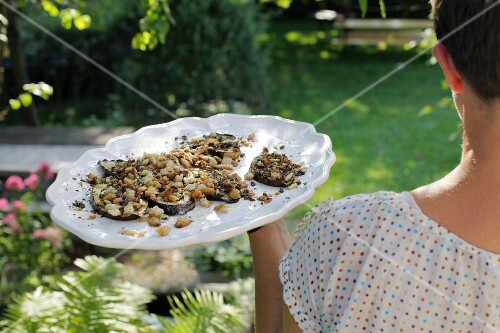 A woman carrying a plate of aubergines and breadcrumbs into a garden