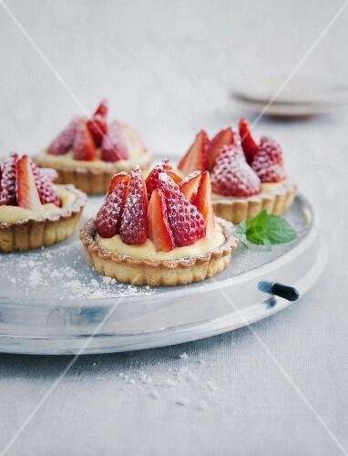 Strawberry tartlets on a cake plate