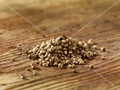 A pile of hemp seeds on a wooden surface