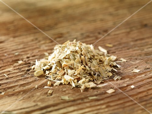 A pile of oat straw on a wooden surface