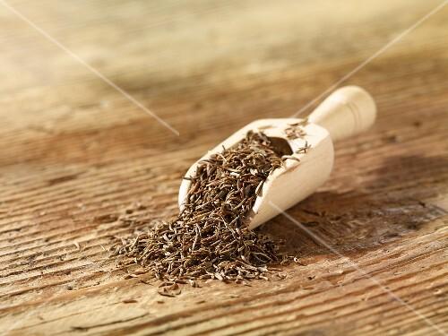 Cumin in a wooden scoop