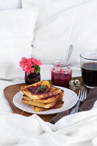Breakfast in bed: French toast with raspberry jam and coffee