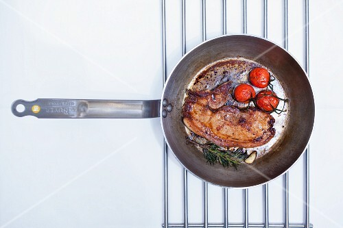 Fried beefsteak with cherry tomatoes and rosemary in a pan (seen from above)