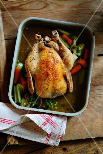 Roast chicken with carrots and leek in a roasting tin
