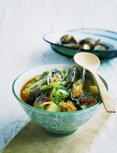 Pointed cabbage stew with mussels in a patterned bowl with a wooden spoon