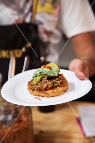A waiter serving a roll with beef and guacamole
