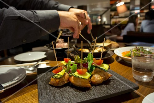 Chicken breast skewers with courgettes and cherry tomatoes in a restaurant