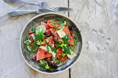 Rocket salad with watermelon, olives, cucumber and sheep's cheese