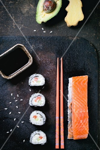 Maki sushi with salmon, avocado, ginger, soy sauce and chopsticks