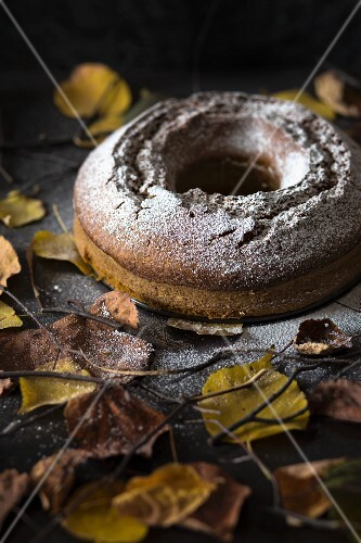 A pumpkin wreath cake surrounded by autumnal leaves