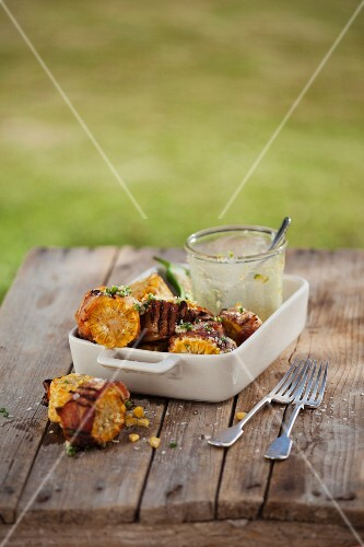 Grilled corn cobs wrapped in bacon