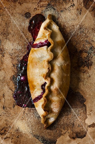 An apple and blueberry turnover on a baking stone