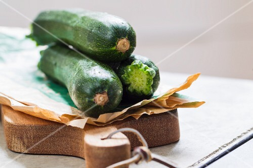 Fresh courgettes with paper on a chopping board