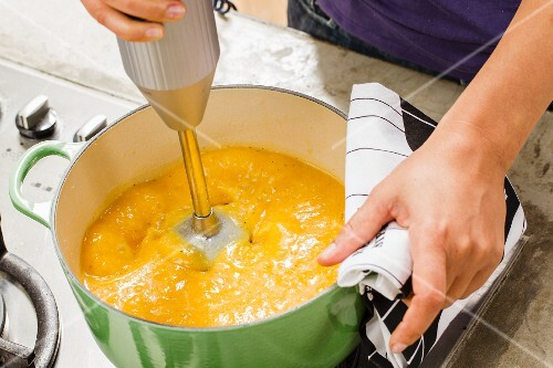 Pumpkin soup being puréed in a pot