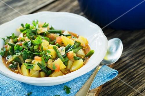 Feeding potato goulash with green beans and savory