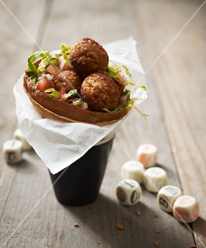 A wheat tortilla filled with vegan millet risotto balls as a takeaway