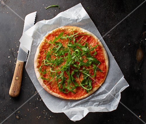 Pizza Margherita with rocket on a piece of paper with a knife