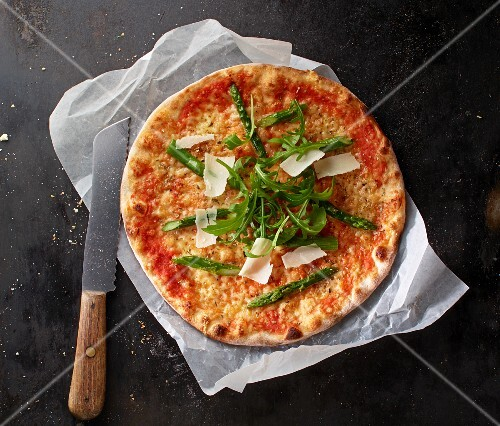 Pizza Margherita with asparagus, rocket and grated Parmesan on a piece of paper with a knife