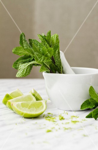 Fresh mint in a mortar, lime wedges and lime zest
