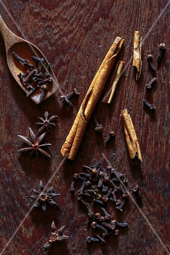 Cinnamon sticks, cloves and star anise on a wooden board (seen from above)