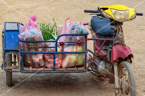 A motorbike with shopping bags in a sidecar (Vientiane, Laos)