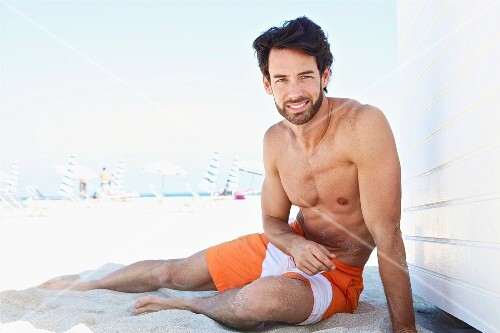 A smiling young man sitting on a beach wearing a pair of swimming shorts