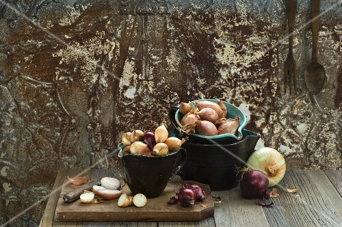 Various types of onions in bowls and chopping board