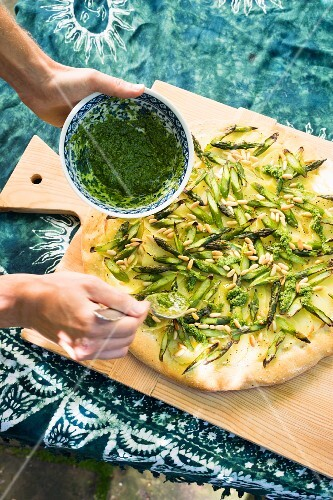 Vegan potato and asparagus pizza being drizzled with wild garlic sauce