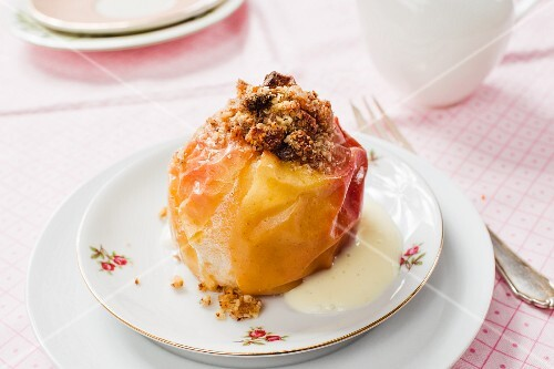 A baked apple with figs, nuts and vegan vanilla sauce