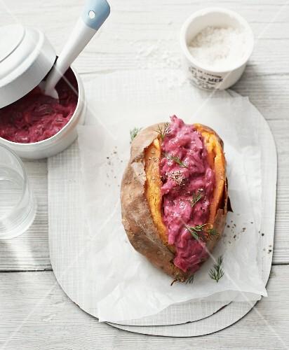 A baked sweet potato with a vegan beetroot soya yoghurt