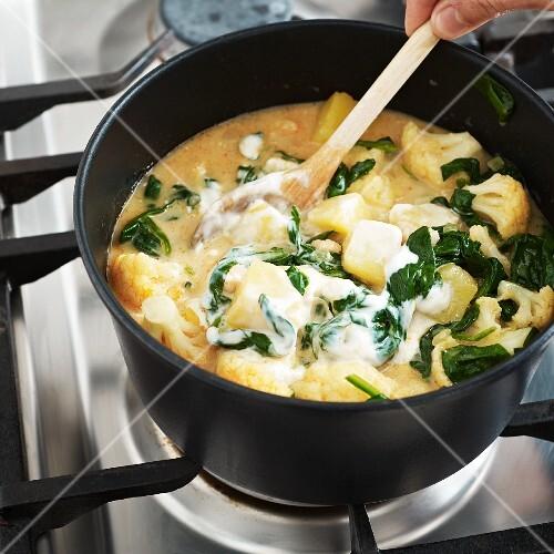 Potato cauliflower curry with spinach being stirred