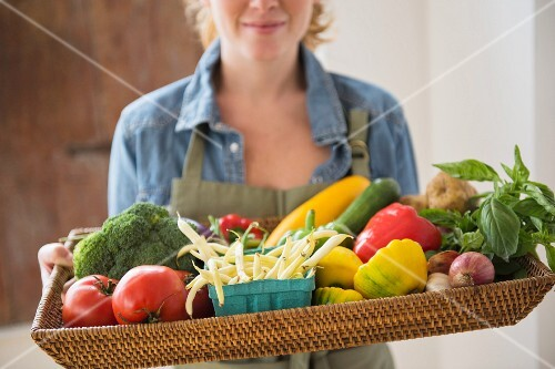 A young woman holding a wicker tray of fresh vegetables