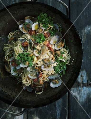 Linguine with clams in a cast iron pan on a dark wooden table
