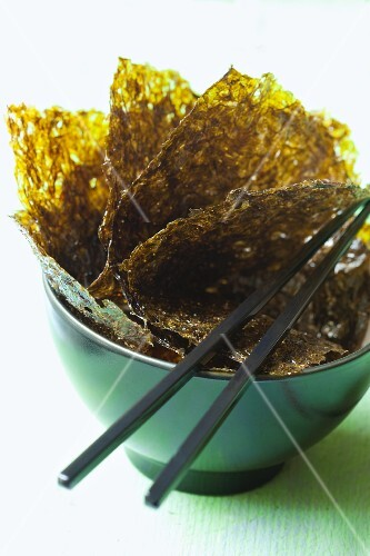 Seaweed leaves in a bowl with chopsticks