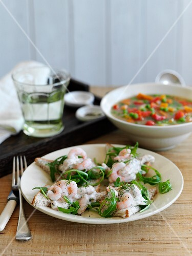 Slices of bread topped with prawns and rocket