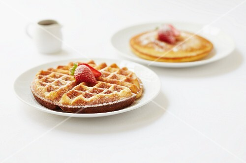 Round waffles and pancakes dusted with icing sugar and topped with strawberries