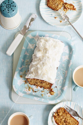 Walnut loaf cake with frosting and grated coconut, sliced