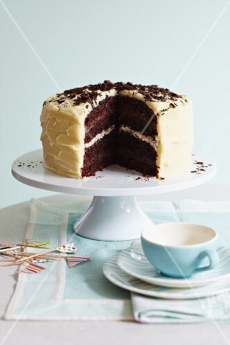 A chocolate celebration cake with a chocolate and vanilla cream filling, frosting and chocolate curls