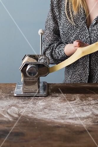 Woman Cranking Pasta Machine; Making Fresh Pasta