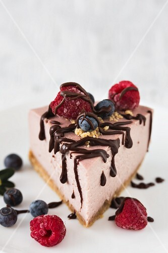 A slice of raspberry cheesecake with fresh raspberries, blueberries and chocolate drizzle