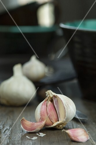 An open bulb of garlic on a wooden table