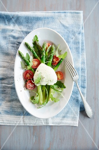 Asparagus mousse on a bed of asparagus with cherry tomatoes