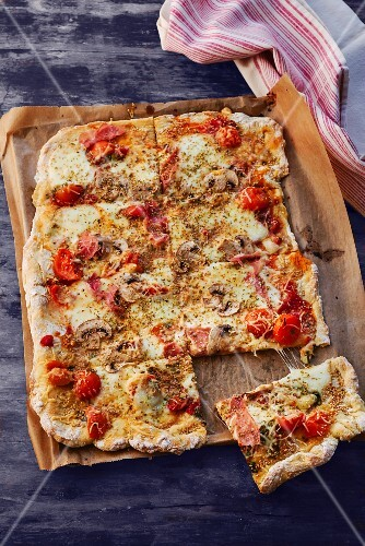 A pizza with ham, mushrooms and tomatoes