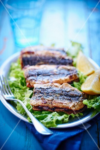 Fried sardines on lettuce with lemons