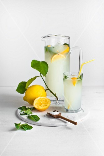 Homemade lemonade with lemons and a wooden spoon of sugar