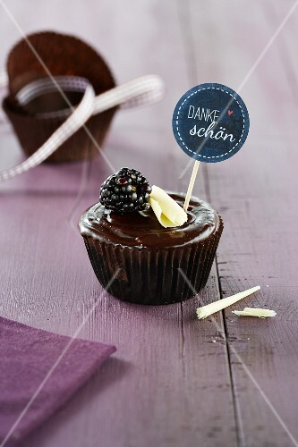 A chocolate cupcake garnished with a blackberry