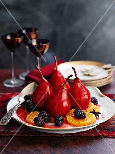Poached red wine pairs with blackberries and orange slices