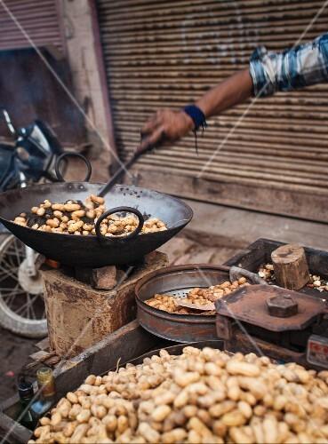 A street vendor cooking peanuts at a market in Varansi, India