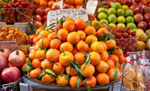 Clementines, pomegranates, tomatoes, apples, dried apricots and dried mango at a vegetable stand in Venice, Italy